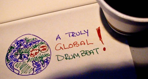 "Text: ""A truly global drumbeat"" Pic: globe w/ dino head on it"